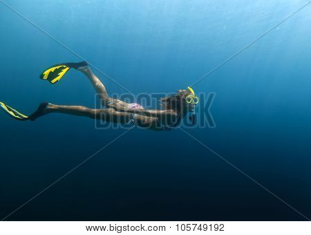 Underwater shot of the lady moving on the breath hold in the depth