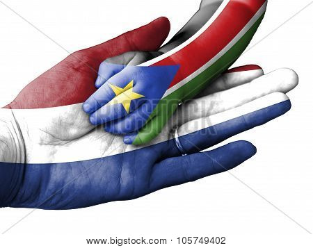 Adult Man Holding A Baby Hand With Netherlands And South Sudan Flags Overlaid. Isolated On White