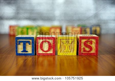 Word Of Toys Spelled With Colorful Wooden Alphabet Blocks.