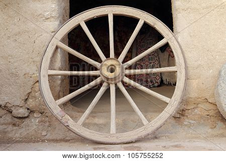 An Old Wooden Wagon Wheel Leaning Up Against Soil Wall