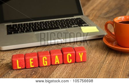 Legacy written on a wooden cube in front of a laptop