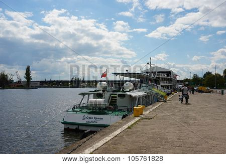 SZCZECIN POLAND - MAY 02 2015: People passing a boat by the Odra river