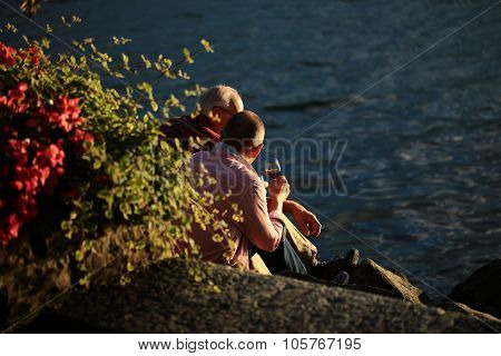 Two Men With Glass Of Vine On Rocks At Seaside
