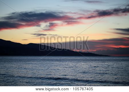 Mountain Silhouette In Sea After Sunset