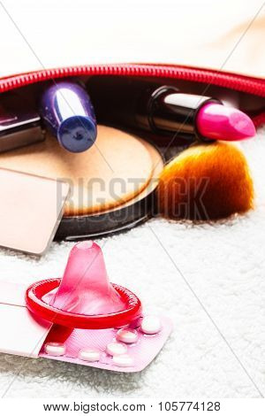 Pills, Condom And Cosmetics In Handbag.