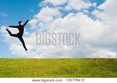 Young Happy Ballerina Jumping High In The Air Over Meadow Against Blue Sky On Sunny Spring Day