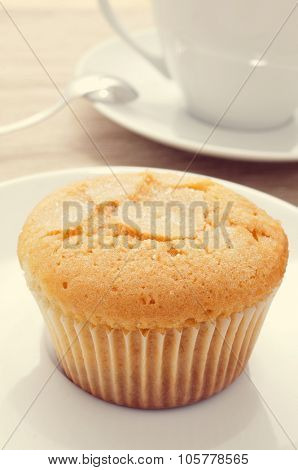 closeup of a magdalena, a typical spanish plain muffin, in a white plate on a set table with a cup of coffee in the background