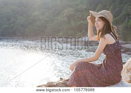 Portrait Of Young Beautiful Woman Wearing Long Dress And Wide Straw Hat Smiling At Sea Side Location
