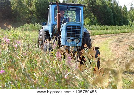 Farming Tractor Working In Field Of Freshly Cut During Hayfield.