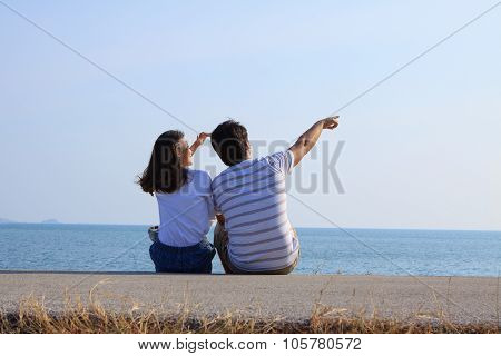 Couples Of Man And Woman Sitting At Sea Side And Point And Looking To Blue Sky