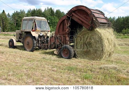 Tractor With Round Baler Collects The Hay To Hayfield.