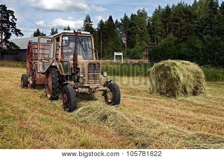 Round Baler Dumping A Freshly Rolled Hay Bale.