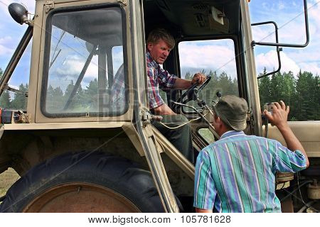 Farmer Talking With Cat-skinner, Which Sits In Cab Of Tractor.