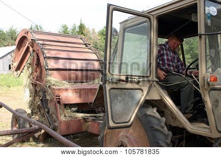 Tractor-driver Operates From The Tractor Hitches Round Hay Baler.