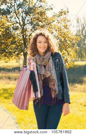 Beautiful young woman with shopping bags and yellow leaves in background