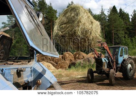Russian Farming, Forklift Truck Loading Round Hay Bales.