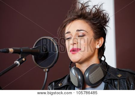 Smiling young woman with eyes closed singing in recording studio
