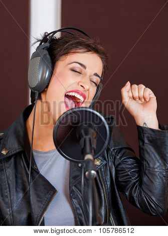 Young female singer enjoying while performing in recording studio