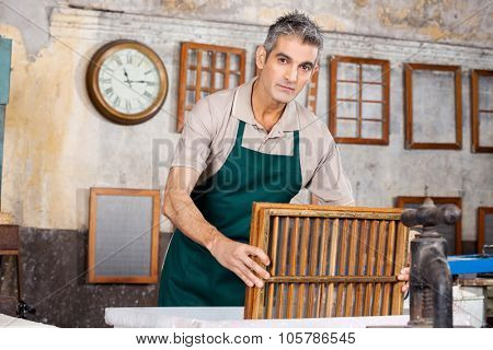 Portrait of mature male worker dipping mold in pulp and water at paper factory