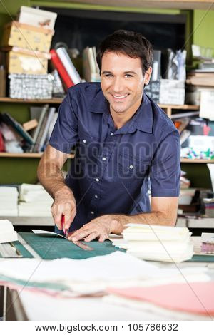 Portrait of mid adult male worker cutting paper in factory