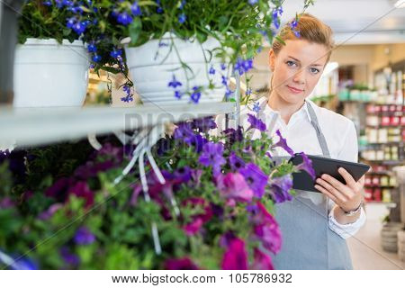 Portrait of confident mid adult florist holding digital tablet while standing by flower trolley in shop