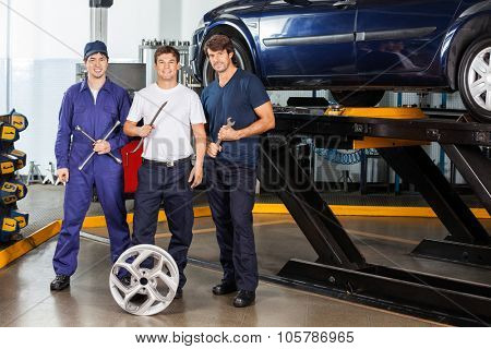 Portrait of confident male mechanics holding tools while standing at garage