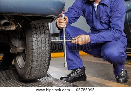 Low section of male mechanic fix car tire with rim wrench at garage