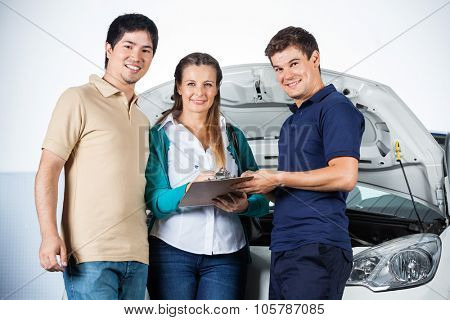 Portrait of happy mechanic taking sign on invoice from customers in garage