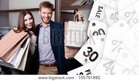 Cheerful couple show their purchases after shopping on sale