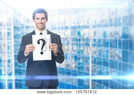 Portrait of businessman handing question mark, blue background. Concept of problem and solution