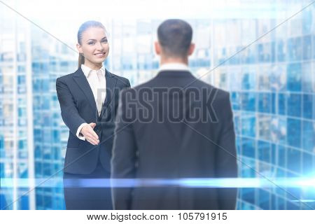 Portrait of handshake gesturing businesswoman and businessman, blue background. Concept of leadership and success