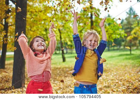 Ecstatic little friends playing with falling leaves in park