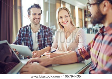 Confident colleagues looking at their co-worker during consultation
