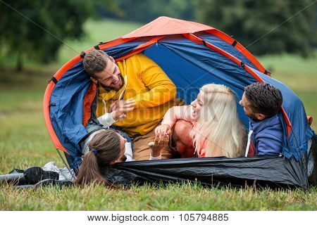 Happy friends in their tent in the countryside