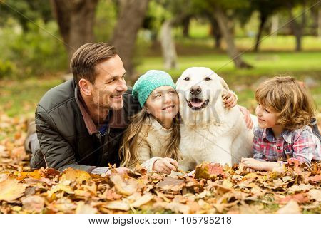 Smiling young family with dog on an autumns day