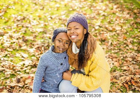 Young mother with her daughter sitting in leaves on an autumns day