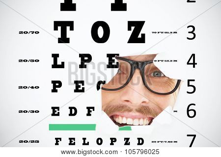 Geeky hipster looking at camera through hole against eye test