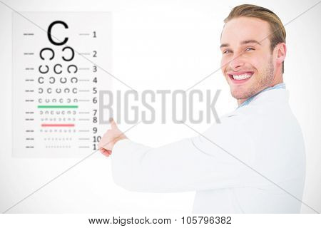 Smiling optician pointing eye test against eye test