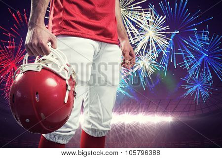 An american football player taking his helmet on her hand against fireworks exploding over football stadium