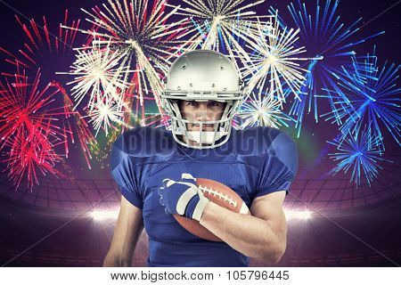 Portrait of American football player holding ball against fireworks exploding over football stadium