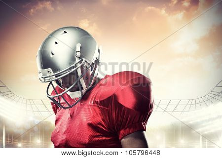 American football player looking down against rugby stadium