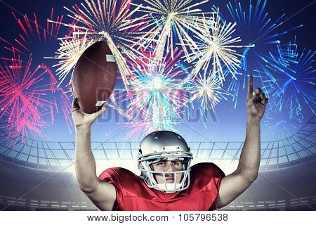 American football player with arms raised holding ball against fireworks exploding over football stadium
