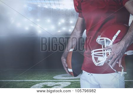 Midsection of player holding rugby ball and helmet against american football arena
