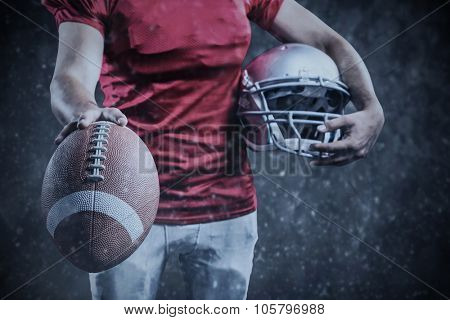 Mid section of sportsman showing American football while holding helmet against black