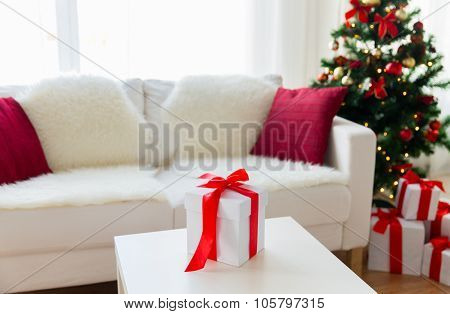 christmas, holidays, winter, celebration and still life concept - close up of gift box on table at home