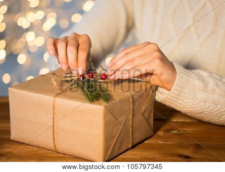 christmas, holidays, presents, new year and people concept - close up of woman decorating gift box or parcel wrapped into brown mail paper with fir brunch