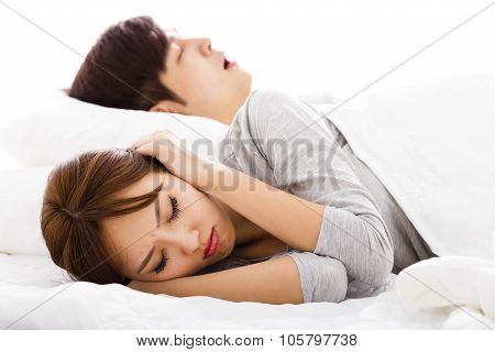 Young Woman Covering Ears  While  Husband Is Snoring