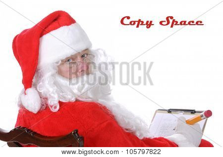 Pleasant middle-aged bearded man in a santa suit with pencil and notepad isolated on a white background