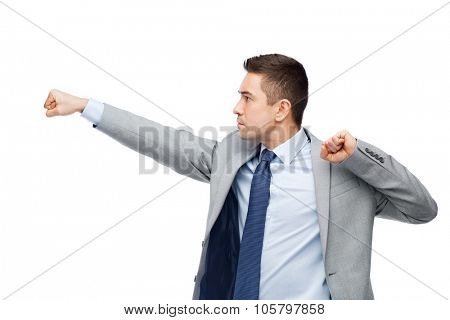 business, people and conflict concept - businessman in suit fighting with someone imaginary