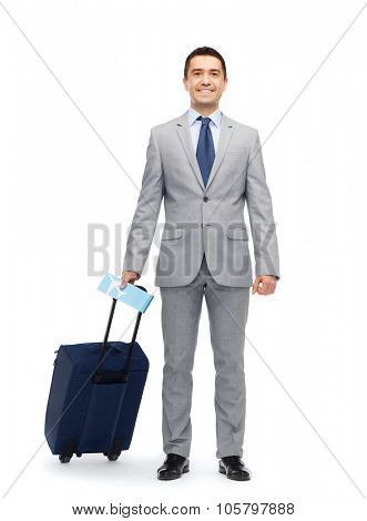 business trip, traveling, luggage and people concept - happy businessman in suit with travel bag and air ticket